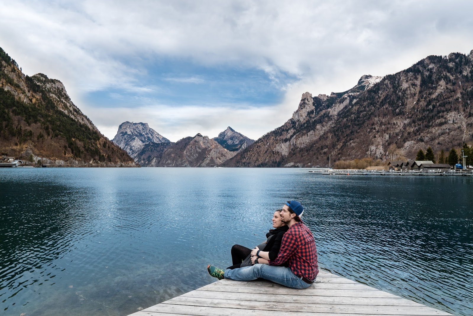 Couple on a boardwalk looking over a lake and surrounded by mountains