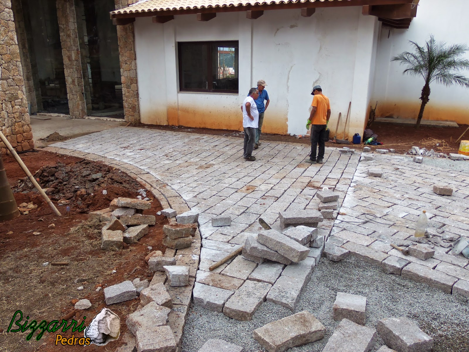 Execução do calçamento de pedra folheta com as guias de pedra folheta.