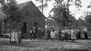 students and teachers outside a one-room schoolhouse in 1890s Florida