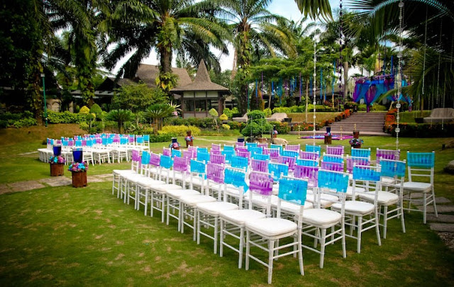 white chairs and purple blue ribbon strips tied