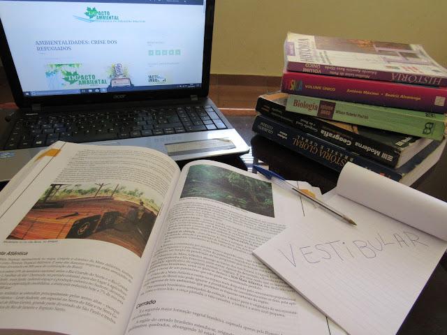 sobre uma mesa, livros de diversas matérias empilhados com um computador conectado ao site do Impacto e um caderno escrito vestibular
