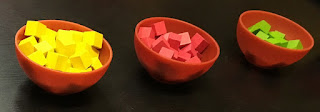 Three of the four colours of cubes: yellow, red, and green. Each colour is contained in a small brown plastic bowl, about five centimeters (two inches) in diameter
