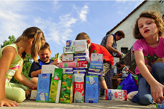 Image: Sand-filled drinks cartons being used as toy building blocks by the children, by Ken Owen, on Flickr