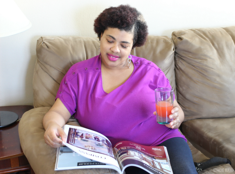 a woman reading with a mocktail in a glass