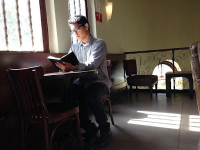Joven estudiando en un lugar público,leyendo en la mesa de un bar junto a la ventana
