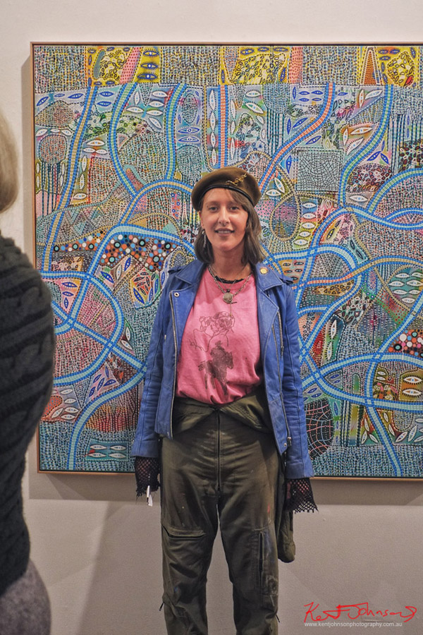 Pinky Blue - Art Student Style at Art House. A beautiful young woman wearing blue leather jacket, pink tee shirth beret with pin, paint smeared engineers dungarees, open fishnet gloves.. Painting by James Ettelson. Photograph by Kent Johnson for Street Fashion Sydney.