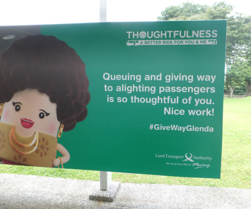 """Queuing and giving way to alighting passengers is so thoughtful of you. Nice work!"" is displayed on a billboard. Below it is the hashtag ""#GiveWayGlenda"" and the words ""Land Transport Authority: We Keep Your World Moving"". Above it are the words ""Thoughtfulness: A Better Ride for You & Me"""