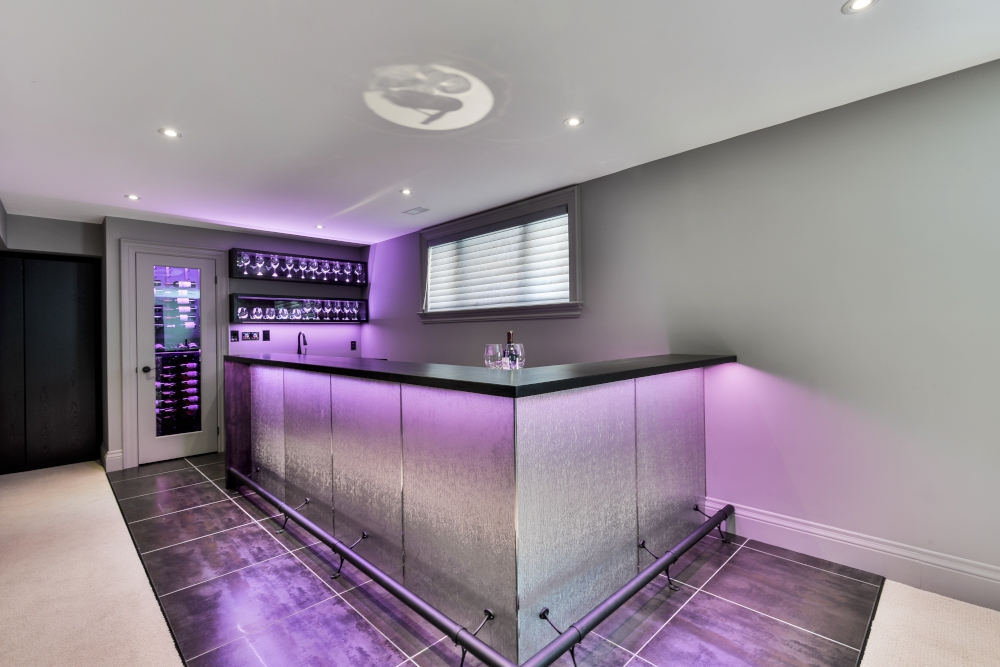 modern L shaped bar in basement with walk in wine cellar