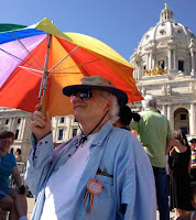 Silver-haired man with rainbow umbrella standing before the Minnesota State Capitols dome and gold horses