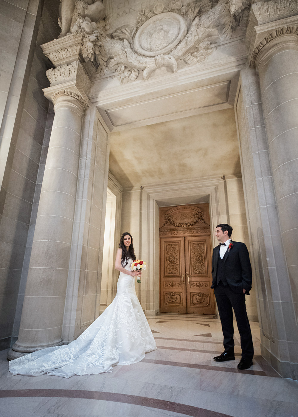 Bride and groom standing in San Francisco City Hall