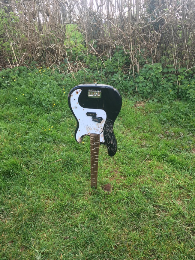 broken-electric-guitar-planted-in-ground