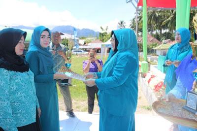 Ketua TP PKK Boltim, Ny. Nursiwin Landjar Dunggio menyerahkan Trophy dan uang pembinaan kepada pemenang lomba cipta menu olahan pangan dari TP PKK Kec. Modayag.