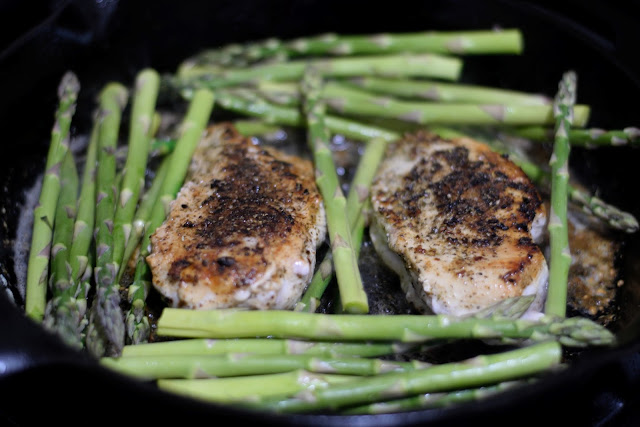 The trimmed asparagus being added to the pan around the chicken.
