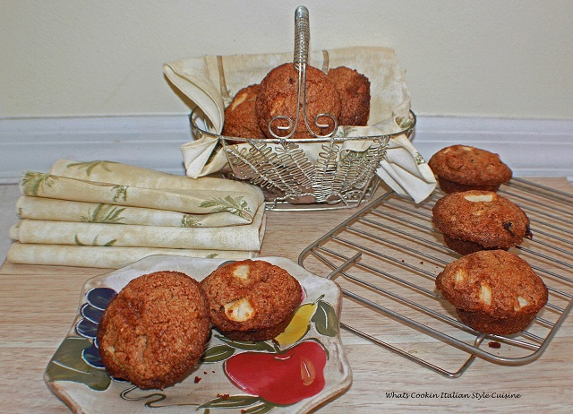 these are muffins cooling on a wire rack and in a wire baskets and some are on the dish with fruit on the plate