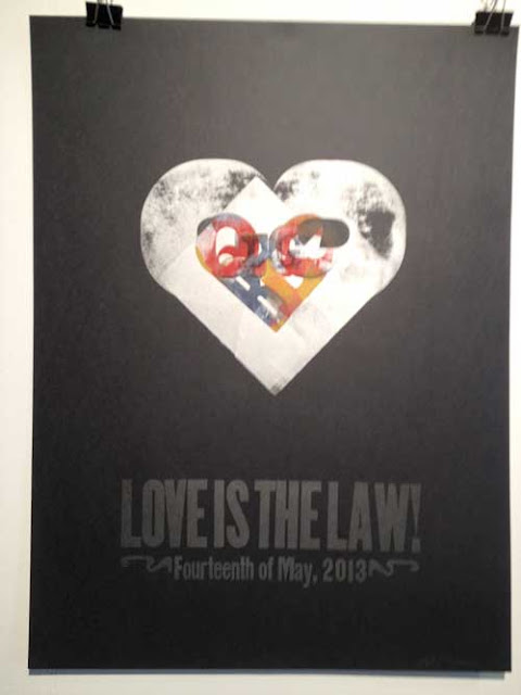 Poster by Bill Moran, black paper with metallic silver heart and other letters overlaid, reading Love is the Law, May 14, 2013
