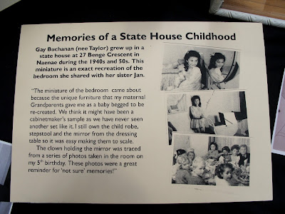 Placard explaining the story behind the miniature 1940s child's bedroom scene 'Memories of a State House Childhood'