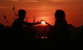 صورة عن الحب: قلب من حبيبين وقت الغروب