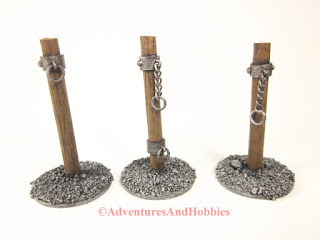 Three styles of pillory posts for 25 to 28 mm scale wargame miniatures.