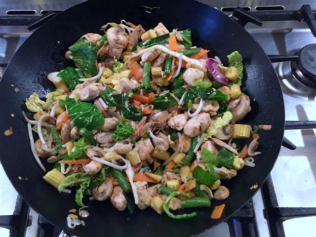stir fry vegetable pack, chicken, baby corn, green beans, and mushrooms frying in a black wok
