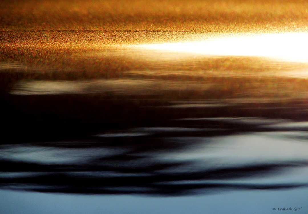 An Abstract Minimalist Photo of the Rays of the setting sun on a cars roof.