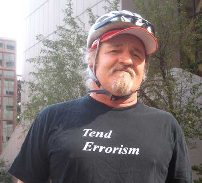 Man with black shirt, white letters, reading Tend Errorism