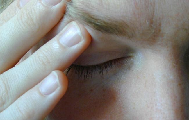Donna con emicrania si massaggia la testa