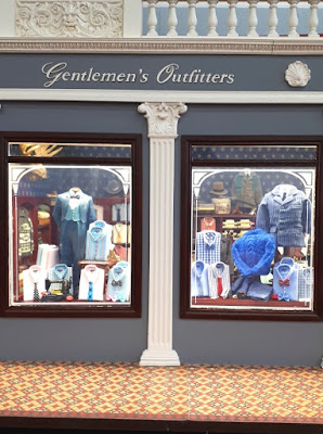 Detail of the front of a one-twelfth scale men's clothing shop with two display windows full of various men's clothing.