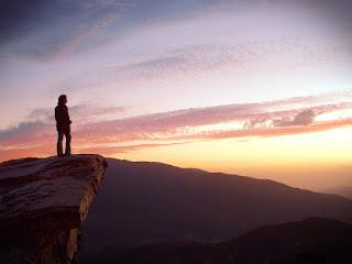 Homem no alto de uma montanha olhand o horizonte