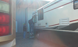 two men with a ladder working on a motorhome