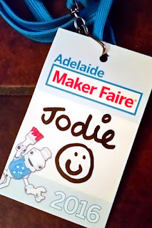 "My exhibitor pass is made of cardboard. Printed on it are the words ""Adelaide Maker Faire 2016"" with a picture of Sam Robot. In black texta is the name ""Jodie"" and a smiley face."