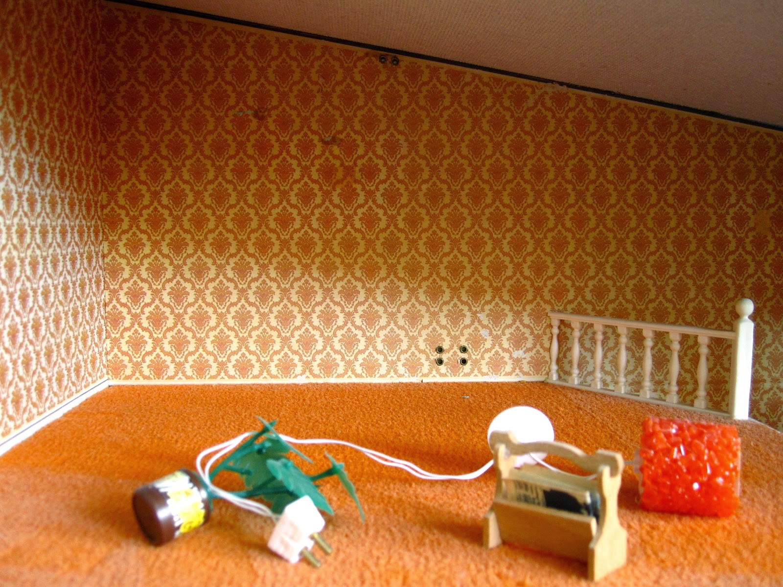 1975 Lundby dolls' house lounge, empty except for a pot plant, a magazine rack and an orange light.