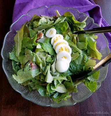 lettuce with bits of bacon and hard boiled eggs waiting for dressing