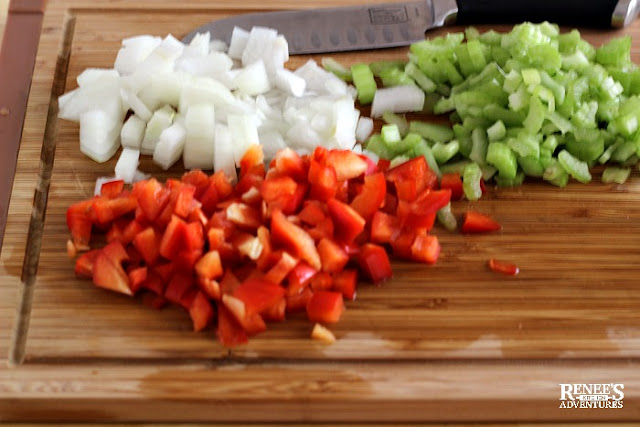 chopped vegetables on wooden board with knife