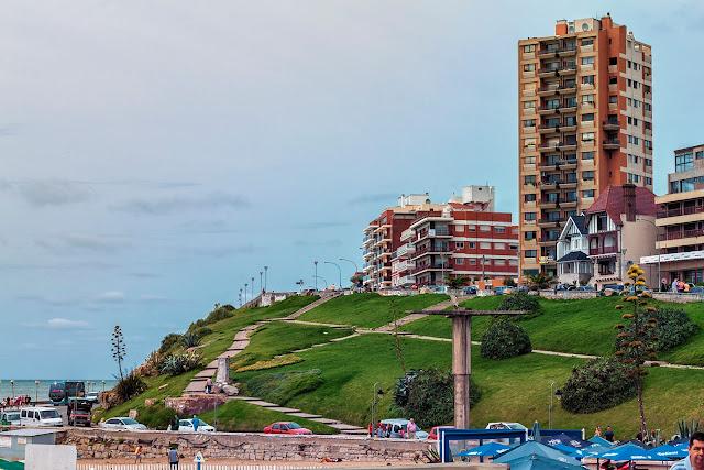 Verde ladera que lleva a los modernos edificios mirando al mar.
