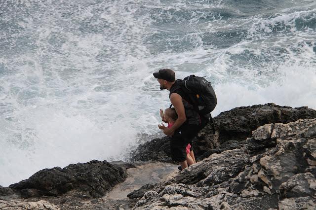 Lapsen kanssa rannalla kun aallot lyö rantakiviin