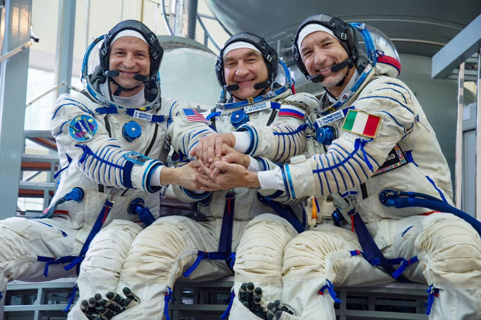 Three astronauts in full gear in training pose for photo