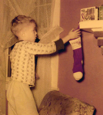 Boy hanging Christmas stocking 1954