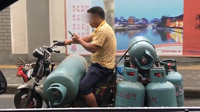 Man carrying seven GAS TANKS on scooter caught playing on phone