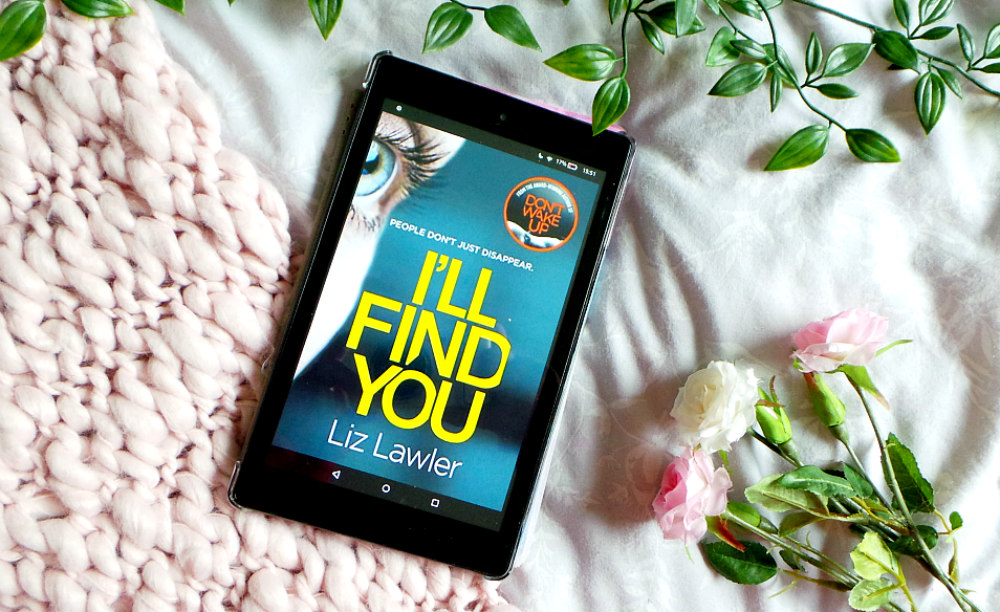 kindle fire with the I'll Find You cover showing. Its resting on a pink chunky knit blanket next to 3 roses