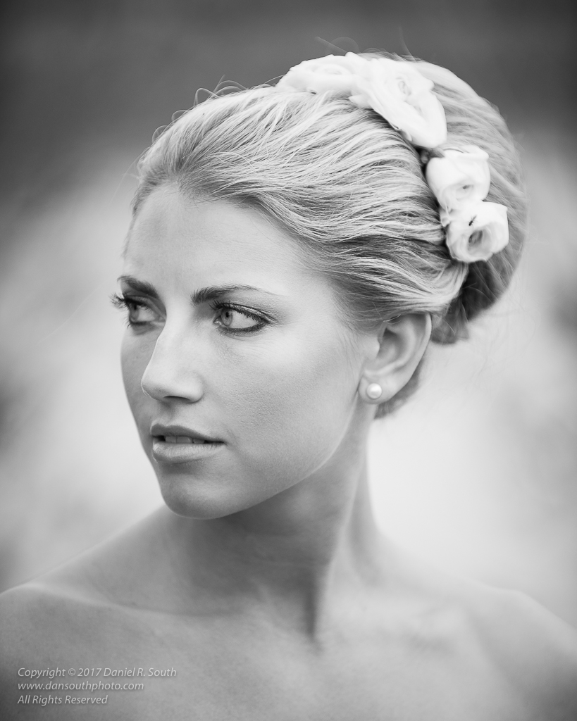 a photo in black and white of a young woman with flowers in her hair