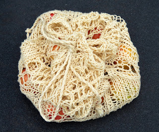 A cream-coloured mesh bag with a drawstring.  The drawstring is pulled closed and has been tied into a bow.