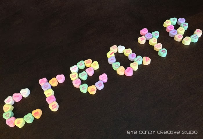 create spelled out with candy conversation hearts, one little word