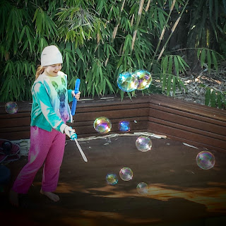 Photo of young girl making giant bubbles in the garden