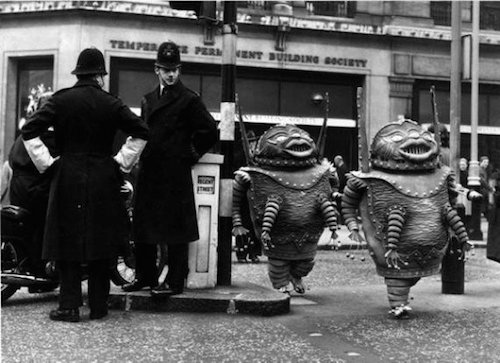1964 photo by Chris Ware of two London police officers watching actors in alien costumes cross the street