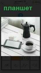 на столе стоят кофеварка и чашка, рядом лежит планшет