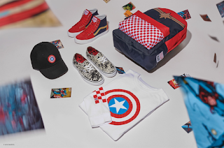 A birds eye group shot of a red and black hi-sk8 shoes, a red, black and checkered backpack, a white top with a red, white and blue circles with a silver star in the middle, a pair of regular laced vans with several colours including red blue and silver, and a black trucker hat with a logo consisting of red, white and blue circles with a silver star on a white background.
