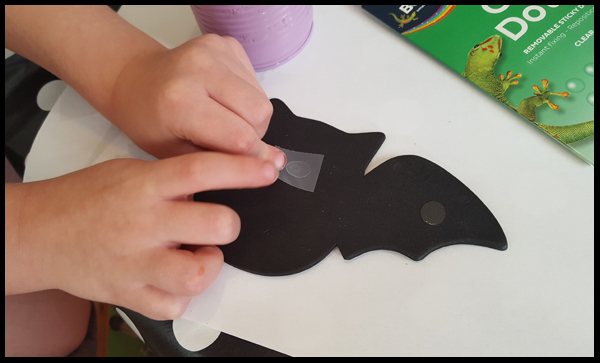adding the glue dots to the can to cover with a bat