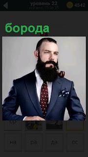 Мужчина в костюме и галстуке с черной длинной бородой. Во рту находится курительная трубка