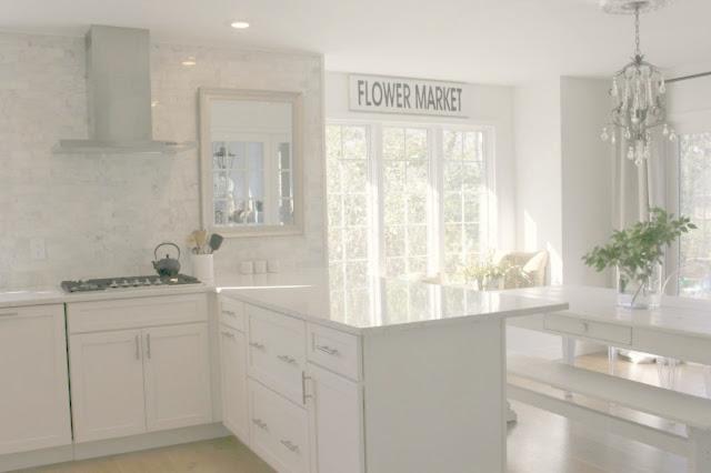 Serene white modern farmhouse kitchen with Minuet quartz countertop and farmhouse table