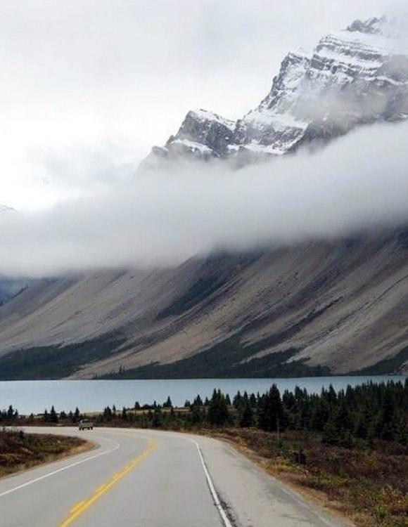 Bulutlarla çevrili bir dağın eteklerindeki bir gölün kenarındaki yolda ilerleyen bir araç